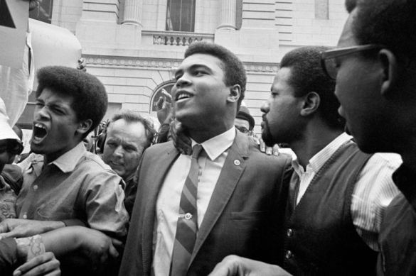Heavyweight champ Muhammad Ali, center, leaves the Armed Forces induction center with his entourage after refusing to be drafted into the Armed Forces in Houston, April 28, 1967. Hundreds of Ali fans and supporters filled the streets to greet him when he left the building. (AP Photo)
